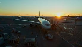 Avion accouplé à l'aéroport sur le coucher du soleil Image stock