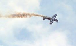 Avion acrobatique aérien Traînée de fumée comme elle fait des cascades Images stock