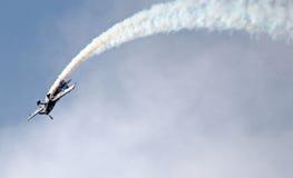 Avion acrobatique aérien Traînée de fumée comme elle fait des cascades Photo stock