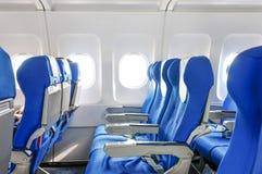Avion avec des passagers sur des sièges Photo stock