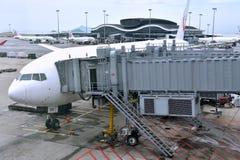Avion avec le canal de chemin dans l'aéroport de Hong Kong Photo libre de droits