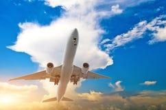 Avion blanc de passager dans le ciel bleu avec des cumulus Images stock