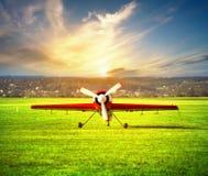 Avion blanc rouge sur l'aérodrome au coucher du soleil Photos libres de droits