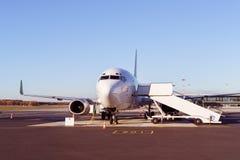 Avion commercial avec la rampe de embarquement reliée Photo libre de droits