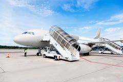 Avion commercial avec la rampe de embarquement reliée Photographie stock