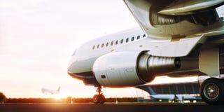 Avion commercial blanc se tenant sur la piste d'aéroport au coucher du soleil L'avion de passager décolle Photographie stock libre de droits