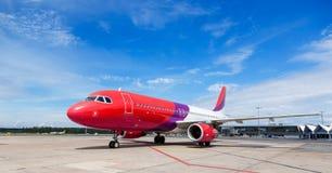 Avion commercial coloré sur la piste avec le ciel bleu Photographie stock libre de droits