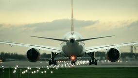 Avion commercial de moteur jumeau commençant le décollage de l'aéroport le soir, vue arrière Photographie stock libre de droits