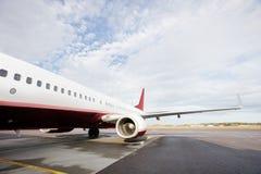 Avion commercial stationnaire sur la piste contre le ciel nuageux Image stock