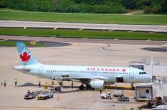 Avion d'Air Canada avec le personnel de piste occupé Image libre de droits