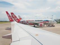 Avion d'AirAsia côte à côte avec l'autre livrée d'Air Asia photographie stock