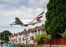 Avion d'Airbus A380 d'émirats débarquant au-dessus des maisons Images libres de droits