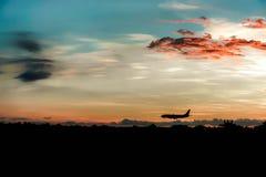 Avion d'atterrissage quand coucher du soleil chaud Image stock