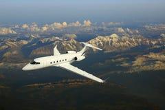 Avion d'avion d'affaires volant au-dessus des montagnes Images stock