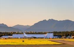 Avion dans l'aéroport avec des arbres et des montagnes sur le fond Images libres de droits