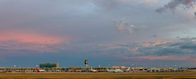 Avion dans l'aéroport et ciel énorme dans le coucher du soleil Photos libres de droits