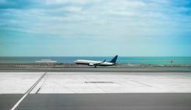 Avion dans l'emballement d'aéroport de Lanzarote avec la mer sur le fond Images libres de droits