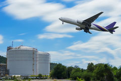 Avion dans le ciel au-dessus des cuves de stockage sur le port d'arrivée ou de départ pour le pétrole avec le bleu Photo stock