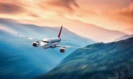 Avion dans le mouvement L'avion avec l'effet de tache floue de mouvement vole au-dessus des collines et des montagnes au coucher  Images stock