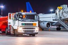Avion de camion de ravitaillement, carburant d'entretien des avions à l'aéroport la nuit Photos libres de droits