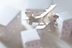 Avion de carton au-dessus de ville de carton Photos stock