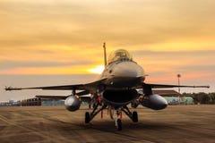Avion de chasse du faucon F-16 sur le fond de coucher du soleil Images stock