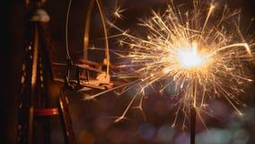 Avion de jouet avec le cierge magique de partie de nouvelle année et les lumières de Noël circulaires abstraites de fond de bokeh Photos stock
