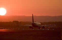 Avion de ligne décollant près du coucher du soleil Image stock