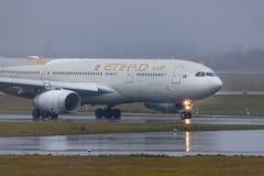 Avion de lignes aériennes d'Etihad sur la terre à l'aéroport Allemagne de Dusseldorf sous la pluie photographie stock libre de droits