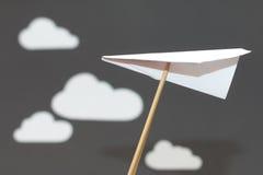 Avion de livre blanc avec des nuages sur un fond gris Photo stock