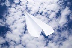 Avion de livre blanc dans un ciel bleu avec des nuages Le symbole de message dans le messager Image libre de droits