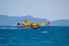 Avion de lutte contre l'incendie prenant l'eau de la mer Images libres de droits