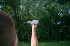 Avion de papier chez des mains des enfants sur le fond de verdure et ciel bleu dans le jour d'été ensoleillé Concept d'été, enfan photo stock