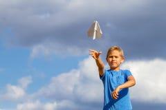 Avion de papier de lancement de garçon contre le ciel bleu photo libre de droits