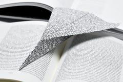 Avion de papier sur un livre ouvert Photo libre de droits