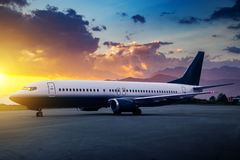 Avion de passager dans l'aéroport au coucher du soleil Images stock