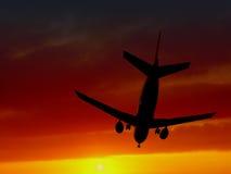 Avion de passager sillhouetted contre le coucher du soleil Photo libre de droits