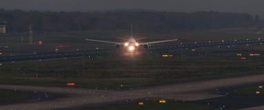 Avion de passager sur une piste d'aéroport le soir Photographie stock libre de droits