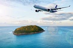 Avion de passagers au-dessus d'île tropicale Photographie stock libre de droits