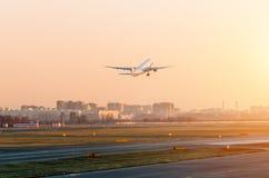 Avion de passagers décollant dans l'aéroport de coucher du soleil de ciel Images stock