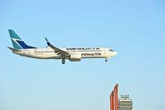 Avion de passagers de message publicitaire de lignes aériennes de Westjet Photographie stock