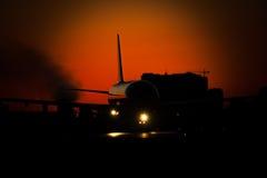 Avion de passagers sur le coucher du soleil Photographie stock libre de droits