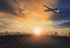 Avion de passagers volant au-dessus du bâtiment urbain contre le beau soleil Photographie stock libre de droits