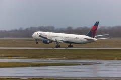 Avion de voies aériennes de delta à l'aéroport Allemagne de Dusseldorf sous la pluie images stock