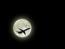 Avion de vol à travers la lune photo libre de droits