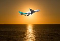 Avion devant le soleil sur la mer au lever de soleil Photos libres de droits