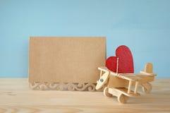 Avion en bois avec le coeur à côté de la carte creeting vierge Photos stock