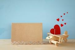 Avion en bois avec le coeur à côté de la carte creeting vierge Image stock