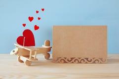 Avion en bois avec le coeur à côté de la carte creeting vierge Photographie stock