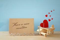 Avion en bois avec le coeur à côté de la carte de voeux Photos stock